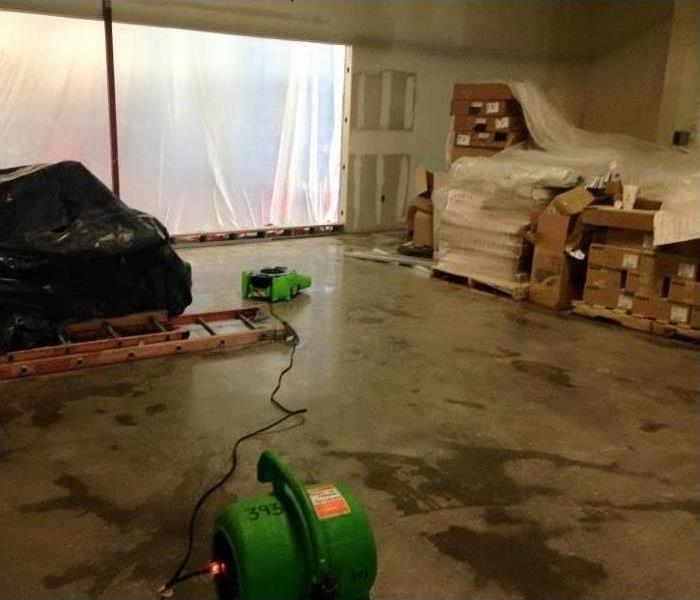 Image shows moisture on a concrete slab on a commercial building with SERVPRO drying equipment in the foreground.