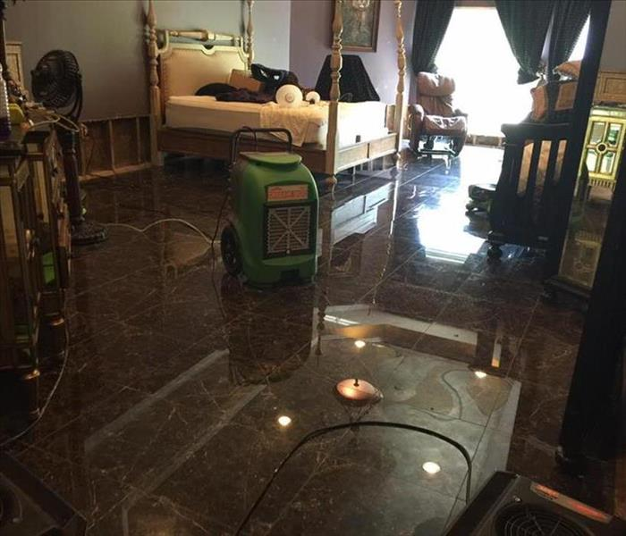 Image shows a dehumidifier in a bedroom on tile floor.