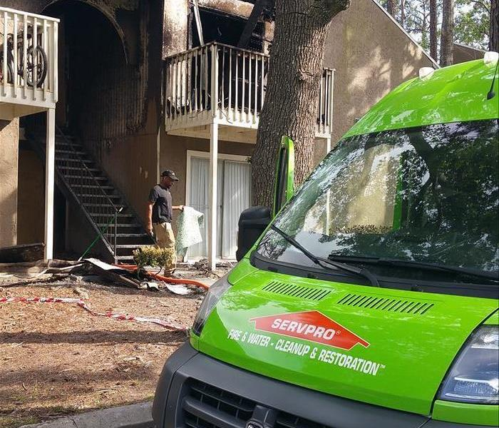 Image shows green van parked in front of a burnt apartment building.