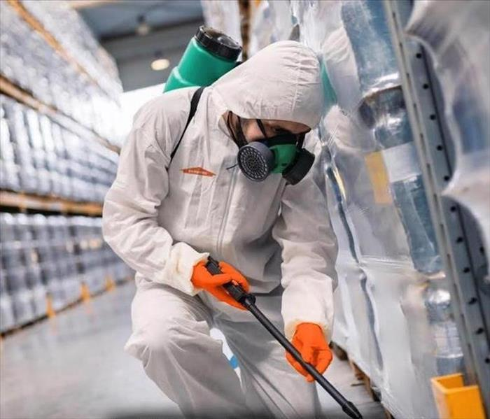 A SERVPRO employee wearing PPE, Tyvec suit, half face respirator, and gloves sanitizes a warehouse.